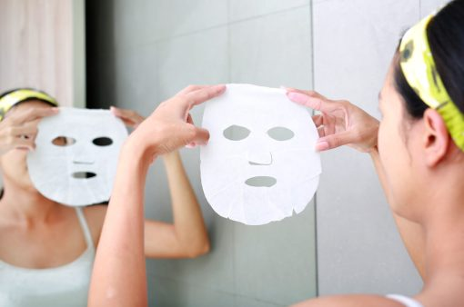 Young woman applying cosmetic facial mask in the bathroom.