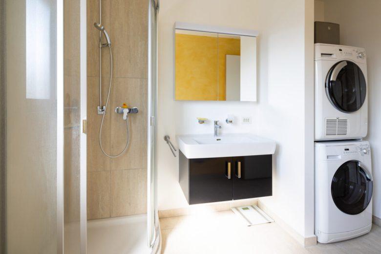 Modern bathroom with shower, black sink, washer and dryer