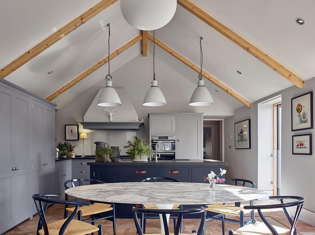 Großzügiger runder Marmor-Esstisch in Galeriewohnraum mit offener Küche
